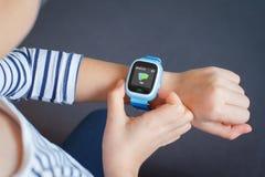 Lilla flickan använder smartwatchtelefonen royaltyfria foton