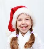 Lilla flickan av fyra år med ett lock på hans huvud Santa Claus Royaltyfri Bild
