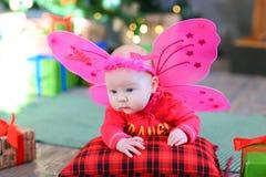 Lilla flickan behandla som ett barn att ligga på kudden med felika vingar Royaltyfri Bild