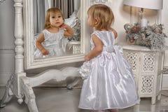 Lilla flickan beundrar hennes reflexion i spegel arkivfoton