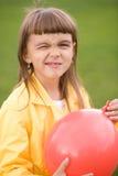 Lilla flickan blåser upp den röda ballongen Arkivbild