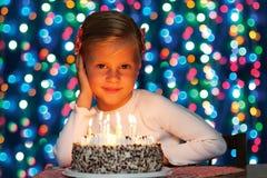 Lilla flickan blåser ut stearinljusen på kakan Royaltyfria Foton