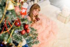 Lilla flickan dekorerar christmassträdet Arkivfoto