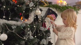Lilla flickan dekorerar en julgran lager videofilmer