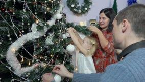 Lilla flickan dekorerar en julgran arkivfilmer