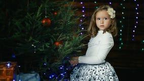 Lilla flickan dekorerar julgranen stock video