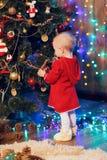 Lilla flickan dekorerar julgranen Arkivbilder