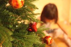 Lilla flickan dekorerar julgranen Arkivfoto