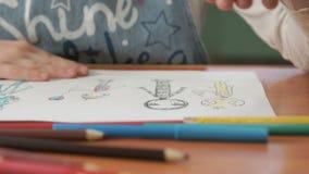 Lilla flickan drar bilderna genom att använda färgblyertspennor lager videofilmer