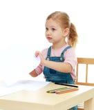 Lilla flickan drar blyertspennor som sitter på tabellen fotografering för bildbyråer