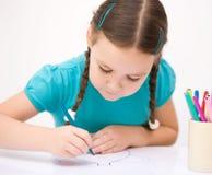 Lilla flickan drar genom att använda blyertspennor Arkivbilder