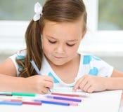 Lilla flickan drar genom att använda blyertspennor Arkivfoton
