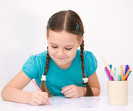Lilla flickan drar genom att använda blyertspennor Arkivfoto