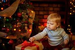 Lilla flickan drar hennes hand till en julklapp royaltyfri bild