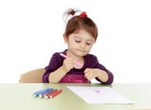 Lilla flickan drar markörer på tabellen royaltyfri foto