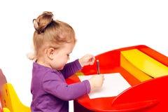 Lilla flickan drar med blyertspennor som sitter på en röd tabell fotografering för bildbyråer