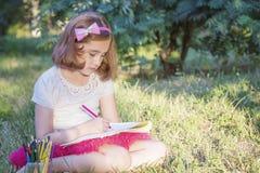 Lilla flickan drar sammanträde på gräset royaltyfri fotografi