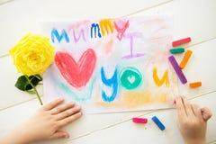 Lilla flickan drar vykortet för moderdag arkivbild