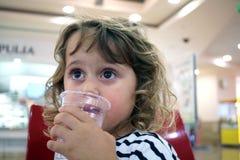 Lilla flickan dricker i gallerian från en kopp royaltyfria foton