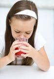 Lilla flickan dricker körsbärsröd fruktsaft Arkivfoto