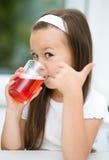 Lilla flickan dricker körsbärsröd fruktsaft Fotografering för Bildbyråer