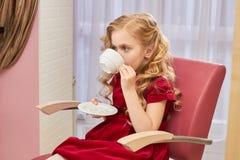 Lilla flickan dricker kaffe Arkivbild