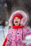 Lilla flickan fångar på en snöflingamun för att gå i parkera Royaltyfria Bilder