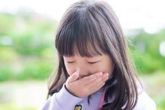 Lilla flickan får förkylning royaltyfri foto