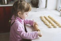 Lilla flickan försöker att rulla ut degen, koncentration royaltyfria bilder