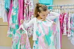 Lilla flickan försöker på klänningen Royaltyfria Bilder