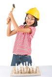 Lilla flickan förstör schackuppsättningen med hammare I Arkivfoton