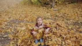 Lilla flickan faller glatt in i en stor hög av gul lövverk arkivfilmer
