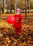 Lilla flickan går i höst parkerar arkivfoton