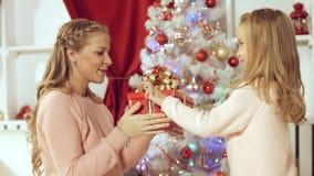 Lilla flickan gör en överraskning till hennes moder för det nya året och ger gåva Arkivfoto