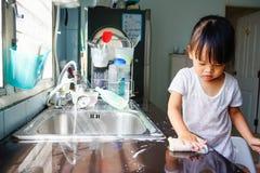 Lilla flickan gör hushållsarbete royaltyfria foton
