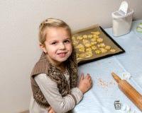 Lilla flickan gör kakor Fotografering för Bildbyråer