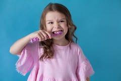 Lilla flickan gör ren den trevliga tandtandläkekonstsjukvården royaltyfri bild