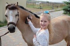Lilla flickan gör ren och kammar hennes ponny och sadlar honom royaltyfria foton