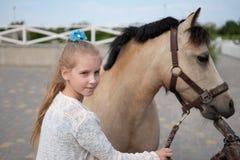 Lilla flickan gör ren och kammar hennes ponny och sadlar honom arkivfoton