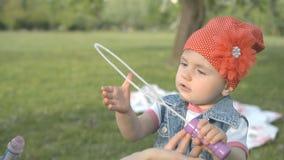 Lilla flickan gör såpbubblan i parkera stock video
