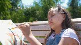 Lilla flickan gör vattenfärgmålning utomhus arkivfilmer