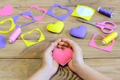 Lilla flickan gjorde prydnader för en filthjärta Flicka som rymmer en filthjärta i hans händer Hantverk för dag för valentin` s e Royaltyfri Fotografi