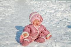 Lilla flickan gråter sammanträde på snö arkivfoto