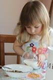 Lilla flickan häller mjölkar Arkivfoto
