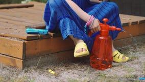 Lilla flickan häller vatten in i vattenballongen på varma sommars dag arkivfilmer