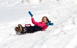 Lilla flickan halkar ner på det snöig berget Arkivfoto