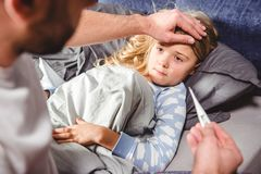 Lilla flickan har en feber och hennes faderkontroller royaltyfri bild