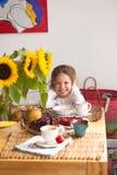 Lilla flickan har frukosten hemma På tabellen är en bukett av blommor av solrosor och en söt paj med frukt, royaltyfri foto