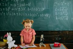 Lilla flickan har kurs i teckning i klassrum på svart tavlabakgrund Varje dag är en kurs royaltyfri fotografi