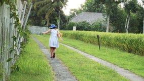 Lilla flickan har rolig spring i solfältet stock video